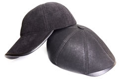 Black velveteen sports cap and black leather cap. On a white background Royalty Free Stock Photos