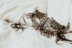 Black venetian mask on bed stock photo