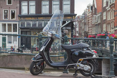 The Black Vespa Scooter is parking in the Amsterdam Stock Photography