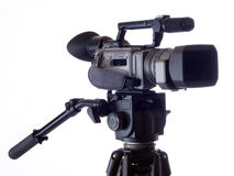 Black Video camera mounted on tripod against white Royalty Free Stock Images