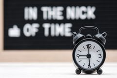 Black vintage alarm clock on the background of signs with the inscription in the nick of time. Black vintage alarm clock on the background of signs with the royalty free stock photo