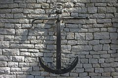 Black vintage anchor hanging on a wall stock image