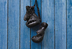 Black vintage boxing gloves hanging on an old rusty nail Royalty Free Stock Photography