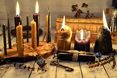 Black and vintage candles with key and vintage clock on old table planks stock photography