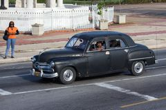 Black vintage car. With passengers moving down the street with a woman on the sidelines Stock Photos