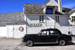 Black vintage car and white scandinavian house Royalty Free Stock Image