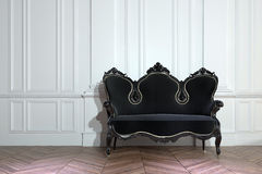 Black vintage couch against a paneled wall Stock Photos