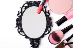 Black vintage hand mirror on white background. Black vintage hand mirror with cosmetics makeup on white background Stock Photo