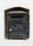Black Vintage Letterbox. A black cast iron letterbox in a white wall niche with an engraving of a horse and knight and the word LETTERS Stock Photography