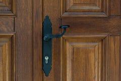 Black vintage metal door handle on brown wooden doors. Doorknob Royalty Free Stock Photo