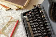 Black vintage metal type writer next to a pile of old note books, pair of eyeglasses and a pencil on a linen tablecloth Royalty Free Stock Image