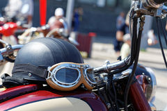 Black vintage moto helmet with glasses on motorcycle Stock Photos