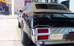 Black vintage muscle car - back view. Black vintage muscle car Cutlass on Custom & Tuning Show. Russia, St. Petersburg, October, 2017.  Back view Royalty Free Stock Images