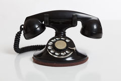 Black, vintage rotary phone on  white Stock Photo