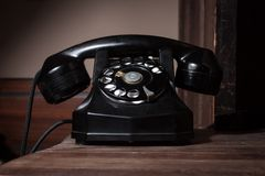 Black vintage telephone. On a wooden surface Royalty Free Stock Photography