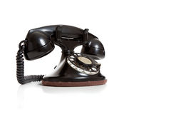 A black vintage telephone on white. A black antique telephone on a white background with copy space Royalty Free Stock Image