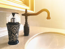 Black vintage water tap and bottle of liquid soap Royalty Free Stock Photo