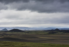 Black Volcanic Landscape Iceland. Volcanic landscape on Iceland with mountains, lava and black sand and dark rain clouds in the sky Stock Images