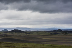 Black Volcanic Landscape Iceland. Volcanic landscape on Iceland with mountains, lava and black sand and dark rain clouds in the sky Royalty Free Stock Photos