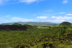 A black volcanic ridge rises out of the green. Royalty Free Stock Images