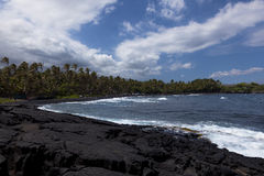 Black volcanic rock forms beach Stock Image