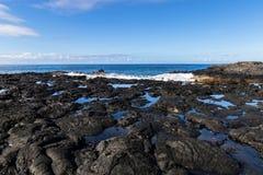 Black volcanic rock on Hawaiian beach near Kona. Tidepools amongst the rock. Waves and ocean in background. royalty free stock photography