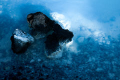 Health Spa Silica on a rock in the famous Blue Lagoon. Black volcanic rocks in the clear water of the blue lagoon in Iceland Royalty Free Stock Photos