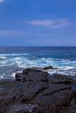 Black  volcanic rocks  on ocean shore Royalty Free Stock Photos