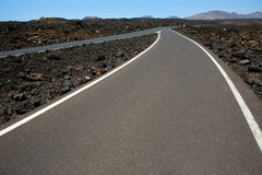 Black volcanic soil and road detail in Lanzarote Stock Photography