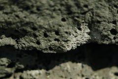 Black volcanic stone selective focus background. Stock Image