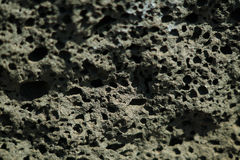 Black volcanic stone selective focus background. Royalty Free Stock Images
