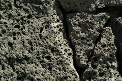 Black volcanic stone selective focus background. Royalty Free Stock Photo