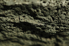 Black volcanic stone selective focus background. Royalty Free Stock Photography