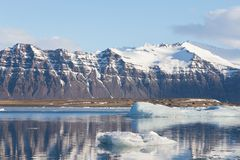 Black volcano mountain over freeze water lake. Iceland winter season natural landscape background Stock Images