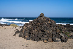 Black volcano stones and white sand on the coastline. Of  the Atlantic Ocean in Canarias Stock Photography