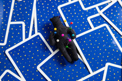 Black voodoo doll on a background of tarot cards. Black voodoo dolls on a background of blue tarot cards Stock Images