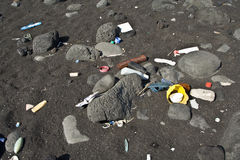 Black vulcanic beach is littered by garbage of cam. Pers and tourists Royalty Free Stock Photo