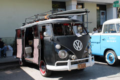 Black VW microbus. Old Volkswagen Microbus carrying surfing boards on roof rack parked outdoors on a sunny Miami day with its side doors wide opened stock images