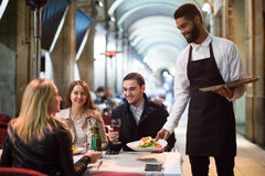 Black Waiter Serving Table On The Terrace Stock Photos