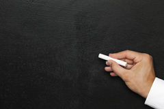 Black wall. Empty blackboard or chalkboard hand with white chalk. Free space Stock Photo