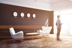 Black wall office lobby with clocks side view, man Stock Image