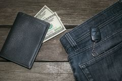 Black wallet, american dolla and key from car in jeans on wooden board. Top view Royalty Free Stock Photo