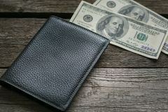 Black wallet and american dollar on board. Royalty Free Stock Photos