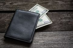 Black wallet and american dollar on board. Royalty Free Stock Photography