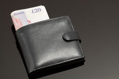 British Wallet. A Black Wallet with British Banknotes in it on a Black Surface Royalty Free Stock Photography