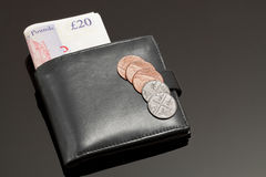 Money. A Black Wallet with British Banknotes and Coins on a Black Surface Stock Image