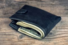 Black wallet with dollars. Black leather wallet with dollars on wooden background Royalty Free Stock Photo