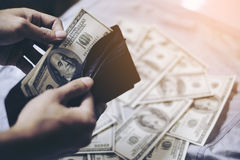 Black wallet with dollars in the hands Royalty Free Stock Photos