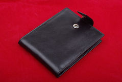 Black leather wallet on red background money purse finance shopping currency object business wealth cash single pay rich personal.  stock photography