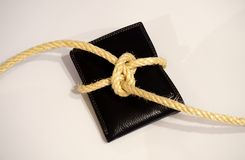 Black wallet tied with a rope. On the white background Stock Photo